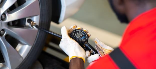Closu up czarny mechanik pompujący oponę na stacji obsługi. sprawdzanie ciśnienia powietrza za pomocą manometru