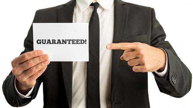 Closuep biznesmen wskazuje na białą kartę ze znakiem gwarantowanym na niej
