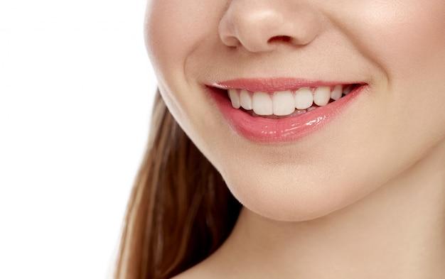Closup śnieżny żeński uśmiech na odosobnionym białym tle