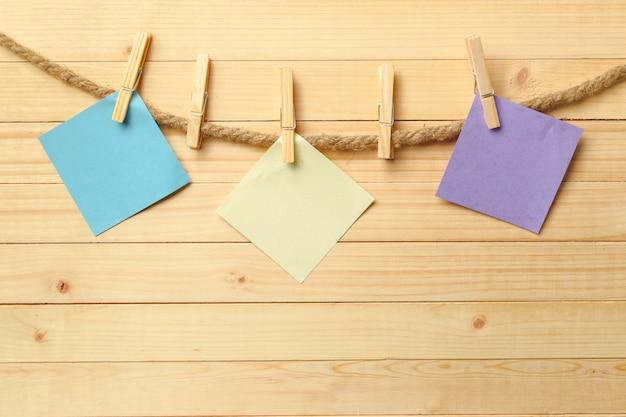 Clothespin obwieszenie z pustym papierem na drewnianym tle