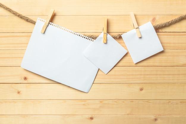 Clothespin obwieszenie z pustym papierem na drewnianym