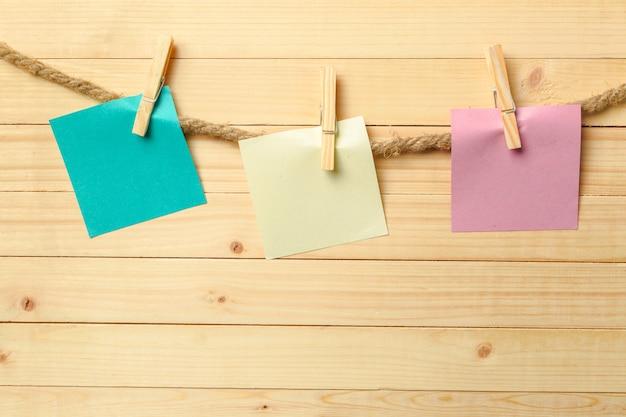 Clothespin wiszące z czystym papierze na drewnianym stole