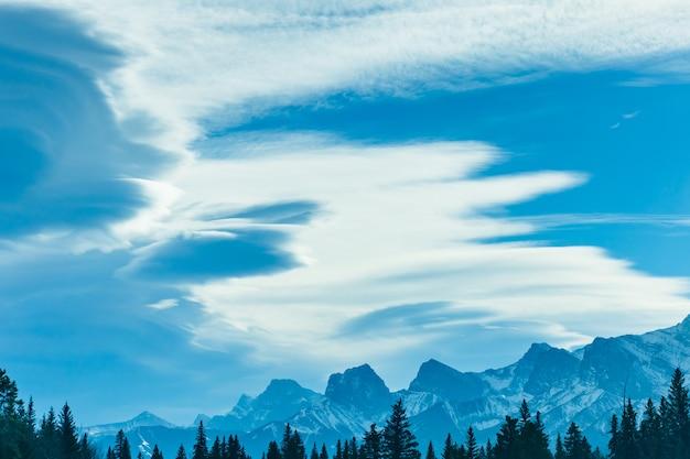 Cloudscape nad lasem. góra z niebieskim niebem i białymi chmurami w tle.