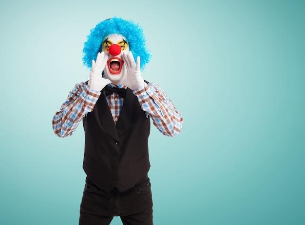 Clown krzyczy z rękami w ustach