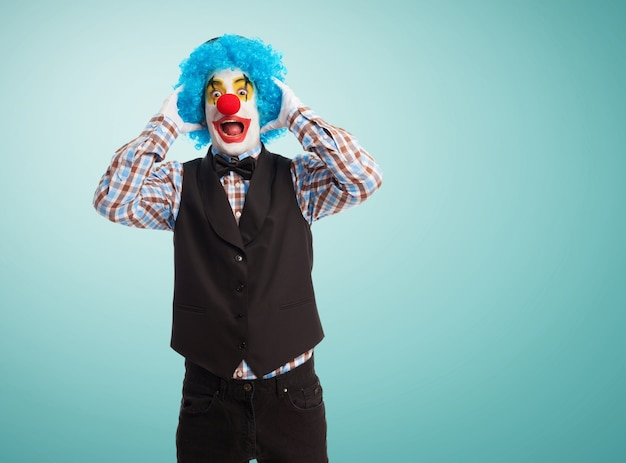 Clown z rękami na głowie