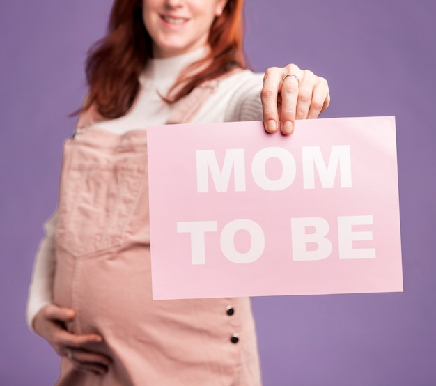 Clsoe-up kobieta w ciąży trzyma papier z mamą być wiadomością