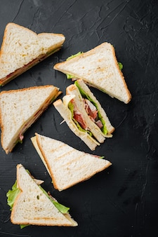 Club sandwich panini z szynką, świeżym pomidorem, serem, na czarnym tle, widok z góry