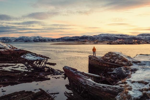 Cmentarz statków, widok zimowego zachodu słońca w starej wiosce rybackiej na brzegu morza barentsa, półwysep kolski