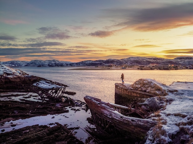 Cmentarz statków, zimowy widok zachodu słońca w starej wiosce rybackiej na brzegu morza barentsa, półwysep kolski, teriberka, rosja.