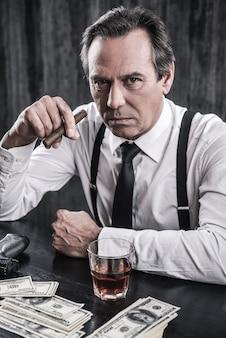 Co chcesz? widok z góry poważnego starszego mężczyzny w koszuli i szelkach siedzącego przy stole i trzymającego cygaro, podczas gdy obok niego leży mnóstwo pieniędzy