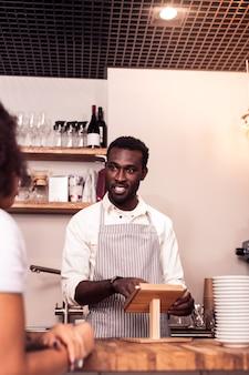 Co chciałbyś zamówić. radosny przyjacielski mężczyzna patrzy na kobietę, pytając ją o zamówienie