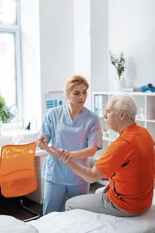 Co czujesz. przyjemna miła pielęgniarka wykonująca masaż podczas pracy z pacjentem