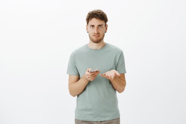 Co do cholery. portret wkurzonego irytującego młodego mężczyzny o jasnych włosach, gestykulującego i trzymającego smartfon, krzywiącego się, oburzonego po przeczytaniu obraźliwej wiadomości