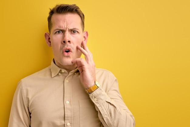 Co do cholery. wstrząśnięty mężczyzna stoi z szeroko otwartymi ustami i oczami, patrząc w kamerę
