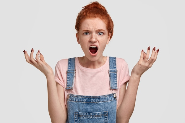 Co do diabła! przygnębiona, zdziwiona rudowłosa kobieta z wściekłym i zirytowanym wyrazem twarzy, rozkłada ręce, woła z irytacją, ma wściekłe spojrzenie, odizolowane na białej ścianie. negatywne emocje