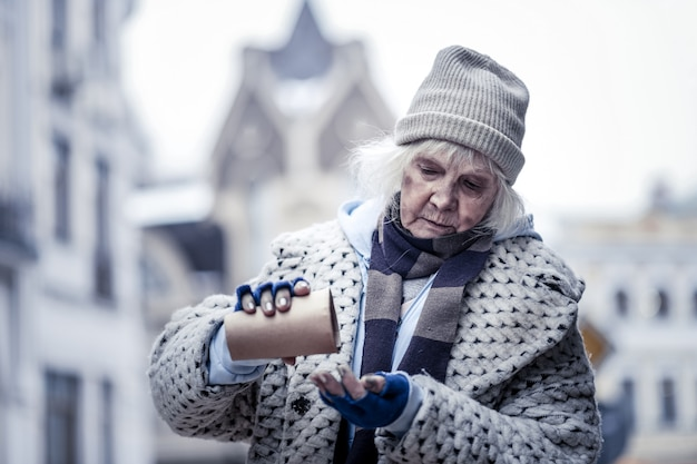 Co ja mam. miła, biedna kobieta przewraca papierową szklankę, sprawdzając, co w niej jest