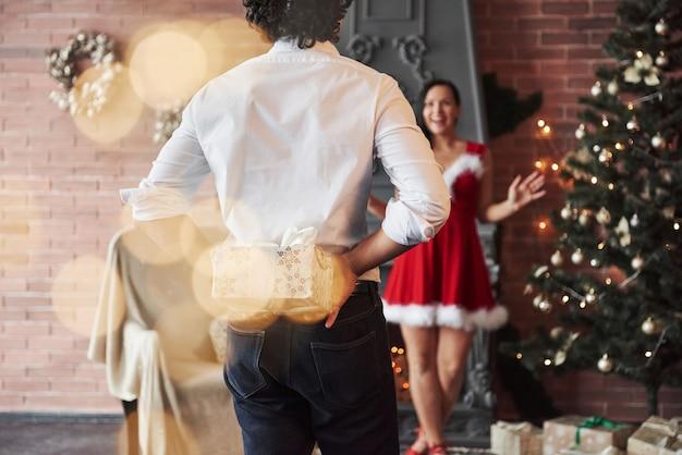 Co masz dla mnie. człowiek stoi i trzyma pudełko za. kobieta w czerwonej sukience otrzyma teraz prezent świąteczny od chłopaka.
