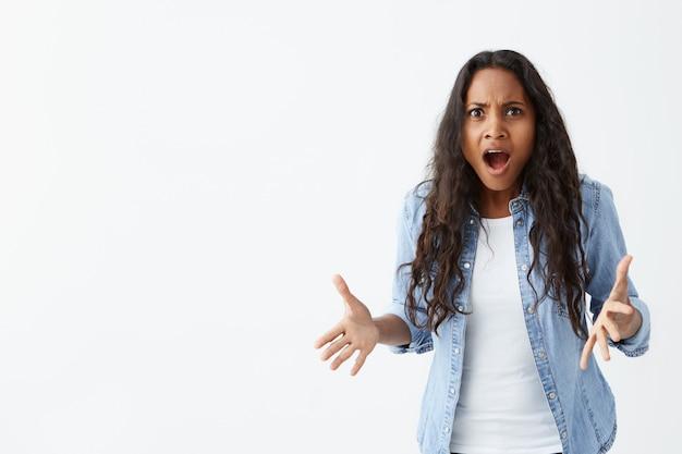 Co?! niezadowolona przedstawia ciemnoskórą kobietę o czarnych falowanych włosach, wzruszającą ramionami w pytającym geście, aktywnie gestykulującą i utrzymującą otwarte usta, mylącą i gniewną.