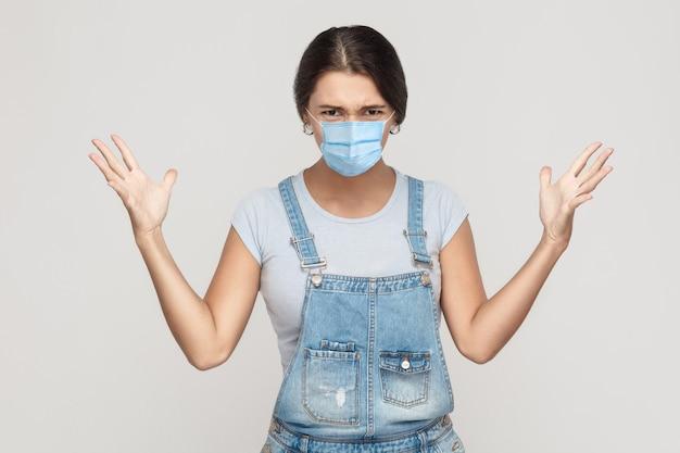 Co? portret zszokowanej szalonej młodej kobiety z chirurgiczną maską medyczną w dżinsowych kombinezonach stojącej, podniesionej ręce i patrzącej na kamerę z gniewną twarzą. kryty studio strzał na białym tle na szarym tle.