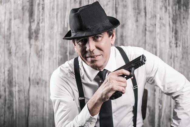 Co teraz powiesz? apodyktyczny starszy mężczyzna w gangsterskim ubraniu, trzymający broń i uśmiechający się, siedząc na krześle przy szarej ścianie
