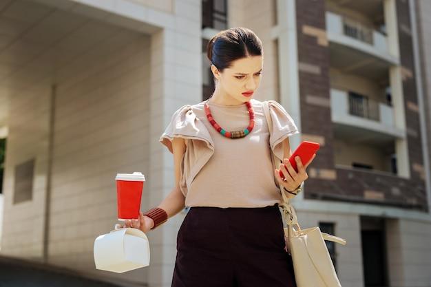 Co to jest. miła młoda kobieta patrząc na ekran swojego smartfona podczas odbierania wiadomości z biura