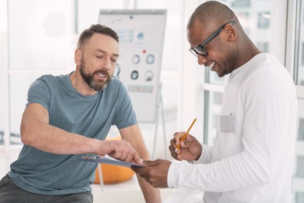 Co to jest. miły miły człowiek wskazujący na notatki podczas zadawania pytań lekarzowi