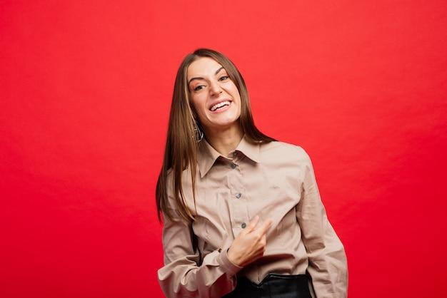 Co to jest. portret kobiety na białym tle na czerwonej ścianie. młody emocjonalny zły, przestraszony kobieta patrząc na kamery ludzkie emocje koncepcja wyrazu twarzy
