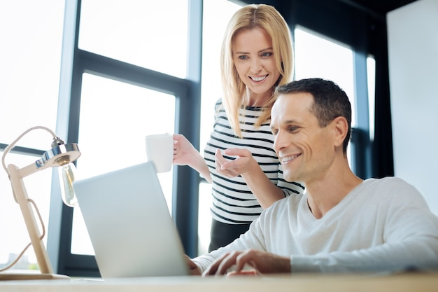 Co to jest. zadowolona pozytywna blondynka kobieta trzyma kubek z herbatą i wskazuje na ekran laptopa, stojąc obok swojego kolegi