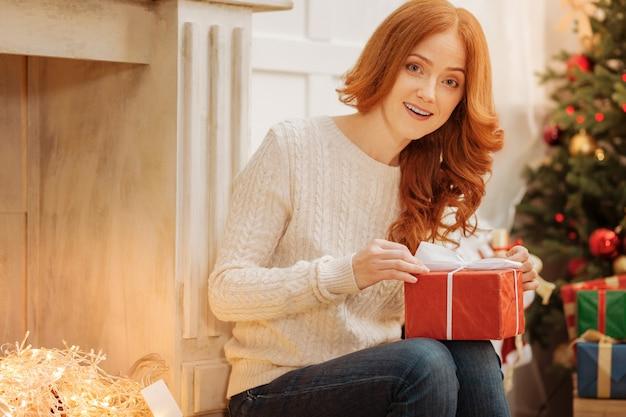 Co tu jest. zaskoczona ruda kobieta siedząca obok ozdobnego kominka otwierająca prezent gwiazdkowy.