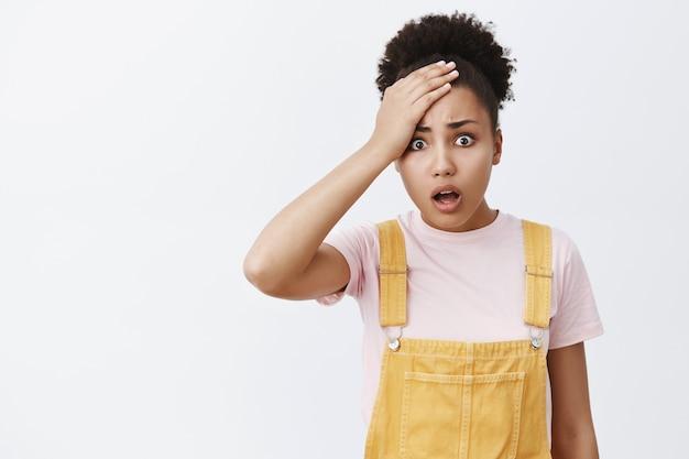 Co ty zrobiłeś. portret wstrząśniętej niezadowolonej i zdenerwowanej siostry afroamerykanki w żółtym kombinezonie, trzymającej dłoń na czole, opadającej szczęki i marszczącej brwi, rozczarowanej i zmartwionej