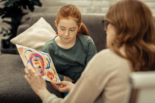 Co widzisz. ładna, ponura dziewczyna patrząca na obraz siedząc z psychologiem