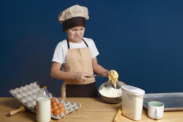 Co za bałagan. rozczarowany chłopiec próbuje ubić jajka mąką i mlekiem podczas robienia samodzielnie ciasta po raz pierwszy, ale ma jakiś problem