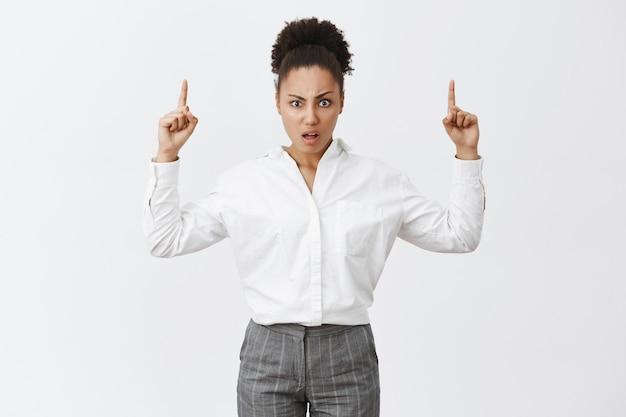 Co za cholera. portret niezadowolonej, zdezorientowanej afroamerykańskiej kobiety z fryzurą kok w białej koszuli i spodniach, wpatrzona w przesłuchanie i rozczarowanie, wskazująca w górę z uniesionymi rękami