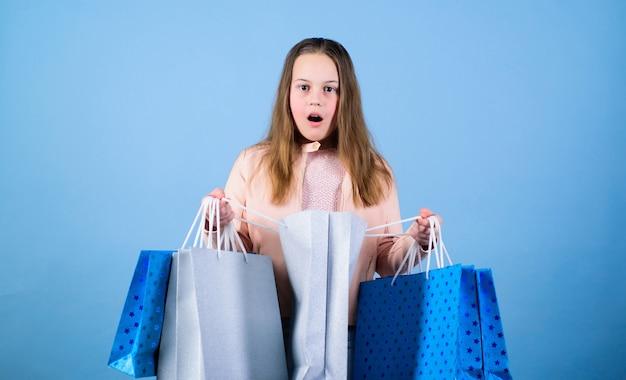 Co za niespodzianka. wyprzedaże i rabaty. mała dziewczynka z torbami na zakupy. oszczędność na zakupach świątecznych. zdziwione dziecko. mała dziewczynka z prezentami. moda dziecięca. sprzedawca z pakietem. przyjemne zakupy.