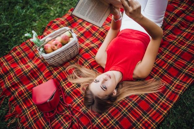 Co za piękny dzień, blondynka czyta książkę na świeżym powietrzu i patrząc w kamerę