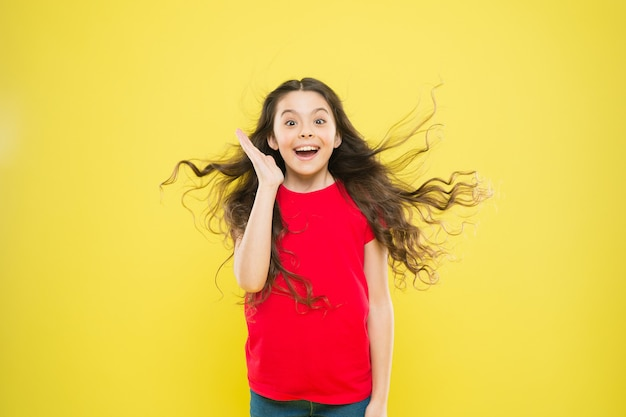 Co za szczęśliwa niespodzianka. zdziwiona dziewczyna na żółtym tle. urocze małe dziecko z niespodzianką na twarzy. śliczna mała dziewczynka trzyma usta otwarte z wielką niespodzianką. cieszyć się z zaskoczenia.