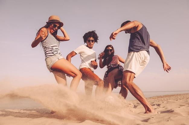 Co za wspaniała gra! grupa wesołych młodych ludzi bawiących się piłką nożną na plaży