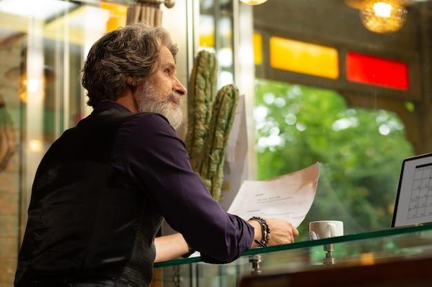Co zamówić. przemyślany brodaty mężczyzna siedzący przy stoliku kawiarnianym z laptopem i filiżanką kawy przy menu wybierając deser.