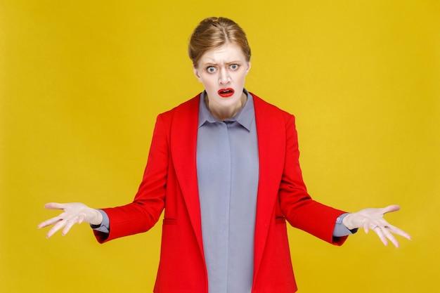 Co zdezorientowana rudowłosa biznesowa kobieta w czerwonym garniturze