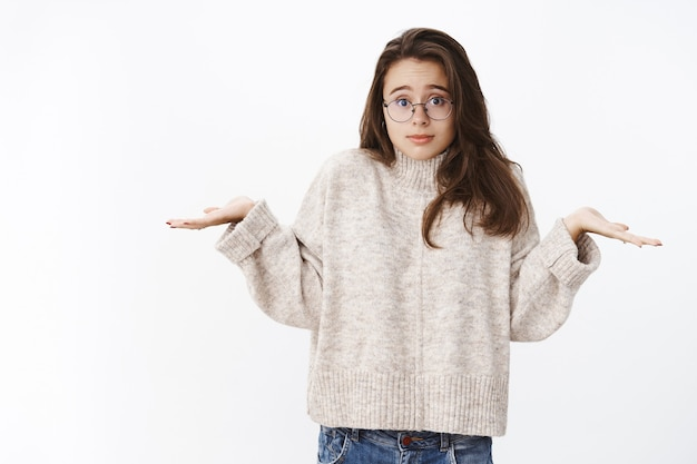 Co zrobiłem źle. niemądra i nieświadoma urocza młoda studentka w okularach i swetrze, wzruszając ramionami rękami na boki i niewinnym spojrzeniem, jako nieświadoma i zdezorientowana nad szarą ścianą.