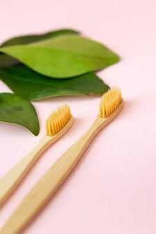 Codzienna higiena człowieka waciki bawełniane i waciki kobieca ręka trzymająca bambusowe szczoteczki do zębów na różu