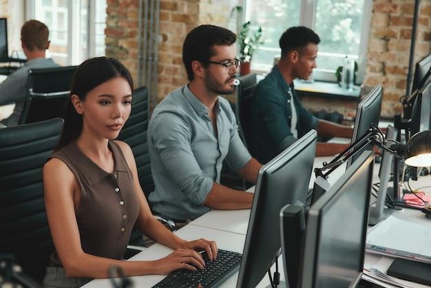Codzienna rutynowa grupa młodych pracowników pracujących na komputerach siedząc w nowoczesnej otwartej przestrzeni