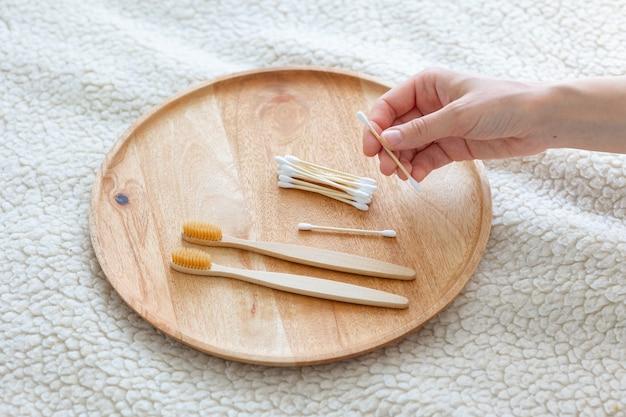 Codzienne waciki do higieny ludzkiej i waciki kosmetyczne ręka kobiety trzymająca bambusowe szczoteczki do zębów na