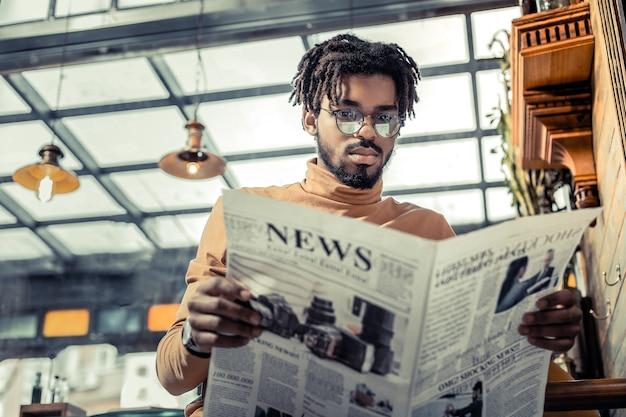 Codzienne wiadomości. poważny brodaty mężczyzna trzyma gazetę podczas analizy artykułu biznesowego