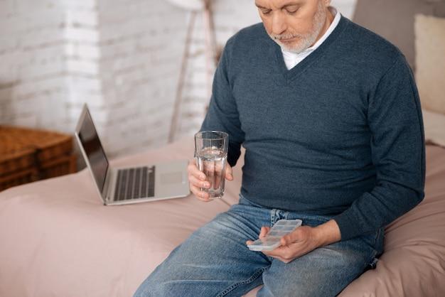 Codziennie. portret starszego mężczyzny, trzymając przypadek z poduszką i szkłem wodnym, siedząc na łóżku.