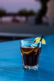 Codzienny koktajl z rumu coli z kostkami lodu i limonką na tle letniego baru