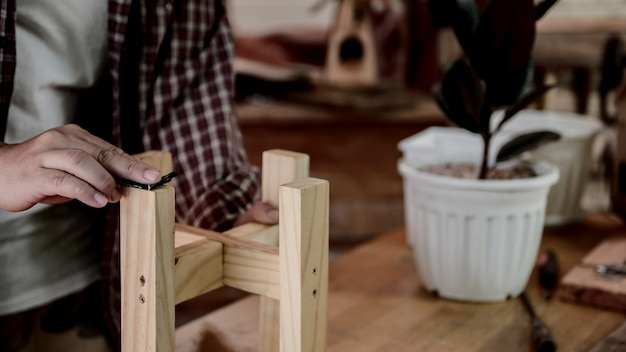 Codzienny styl życia człowieka w domu. stolarka drewniana i diy vintage drewniana półka na doniczki do dekoracji ogrodu. warsztat stolarski i rzemieślniczy.