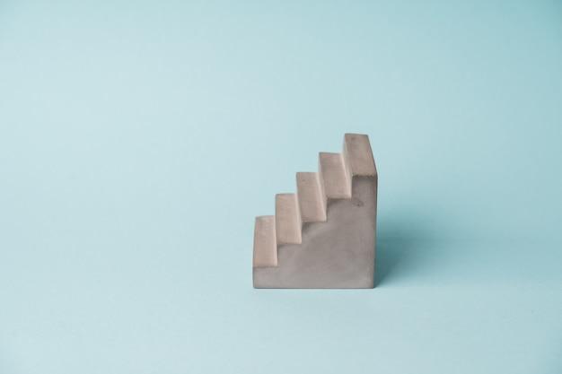 Cokół betonowy starirs na niebieskim tle. koncepcja minimalnego wzrostu. skopiuj miejsce. etap dla produktów