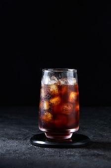 Cola mrożona lub zimna kawa w wysokiej szklance na ciemnym tle. koncepcja orzeźwiający napój latem.