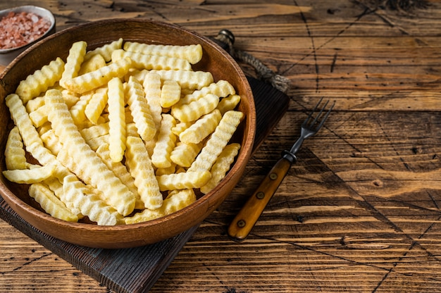 Cold frozen crinkle piekarnik frytki ziemniaczane paluszki w drewnianym talerzu. drewniane tło. widok z góry. skopiuj miejsce.